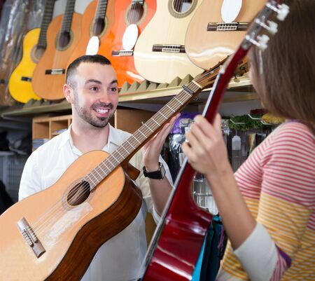 Positive young customers choosing new guitar in store and smiling