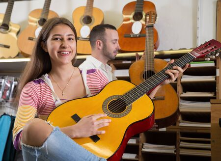 Smiling girl playing acoustic guitar in music shop