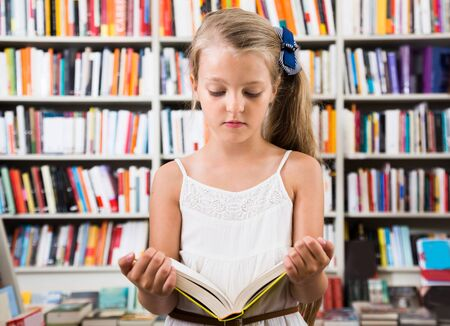 considers: beautiful girl child considers the book in a bookstore