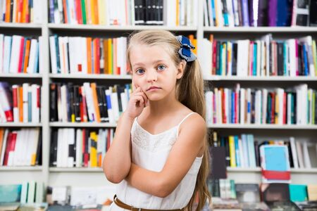Prodigy: pensive blond girl child puzzled of selection of books in the store
