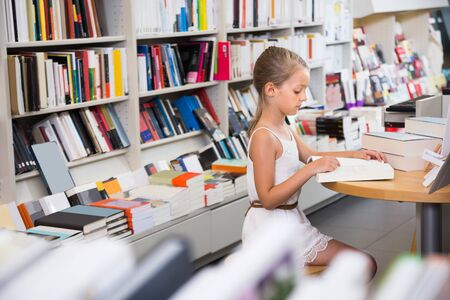 Prodigy: studious smart girl child is engaged with a book in the library