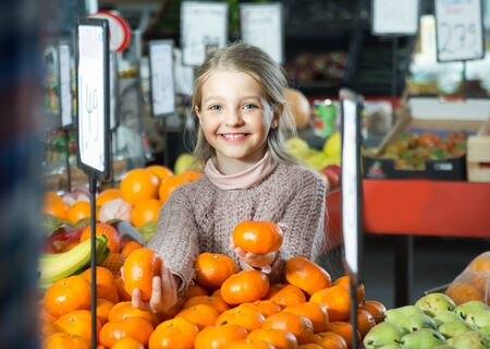 purchasers: positive little girl buying mandarins in shop Stock Photo