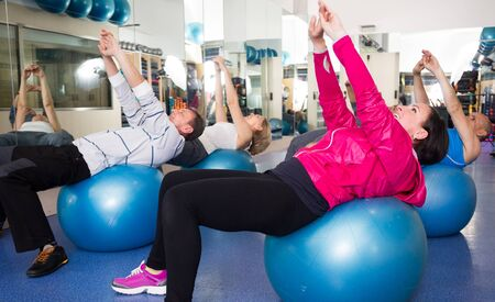 active adult community: smiling mature men and women involved in sports gym