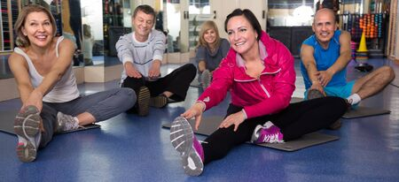 active adult community: smiling elderly people doing exercise on mat in modern gym Stock Photo