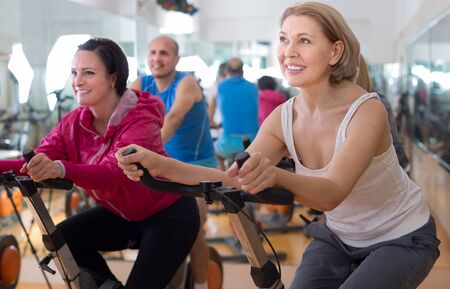 satisfied older people do sports on exercise bikes