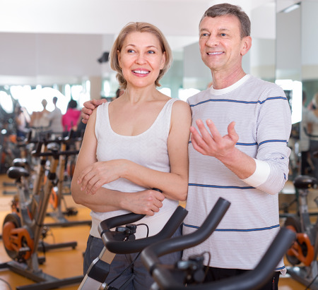elderly man and smiling woman in background bikes at the gym. focus on woman