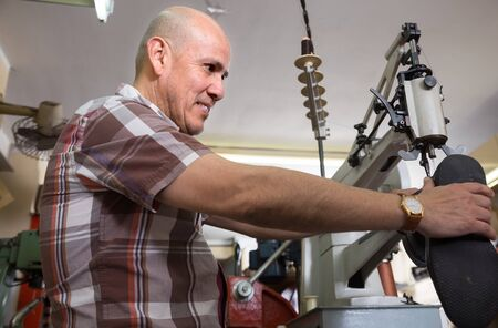 broaching: Elderly shoemaker stitching shoes on leather sewing machine at factory Stock Photo