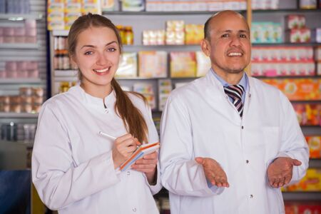 overalls: Portrait of two friendly specialists working in drugstore Stock Photo