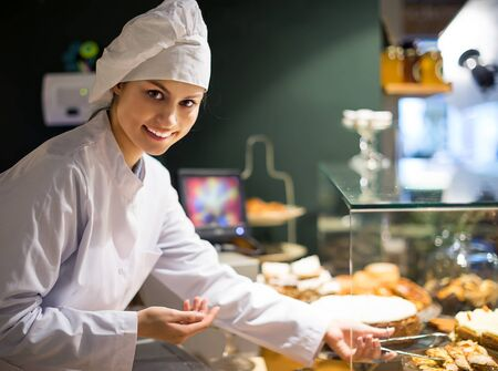 young girl offering bread and different pastry for sale Stock Photo