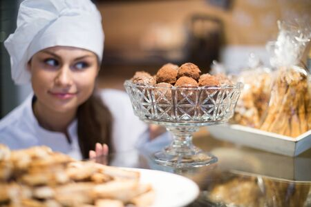 positive female selling tarts and sweet pastry in coffee-house Stock Photo