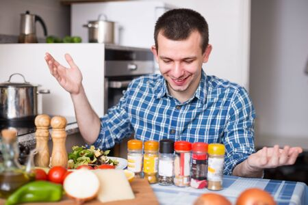 Housekeeping an ordinary male chooses spices in the kitchen at home Stock Photo