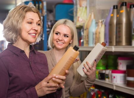 mother and adult daughter in good spirits selecting shampoo in the store