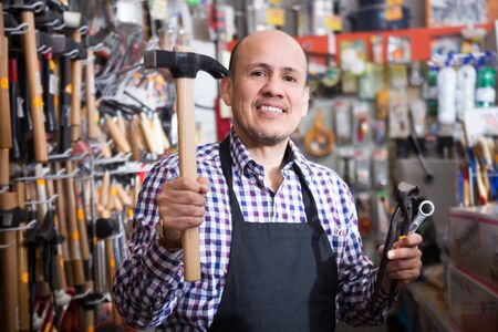 Mature male seller offering hammer in household shop Stock Photo