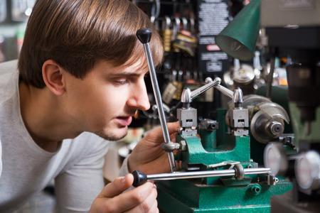 Gewone klusjesman het maken van kopieën van de deur sleutels in slotenmaker Stockfoto - 69015508