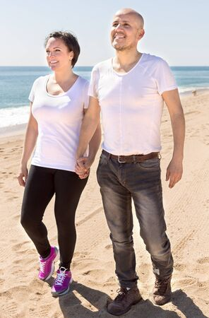 couple of elderly man with a woman in white shirts walking on sand on beach Stock Photo