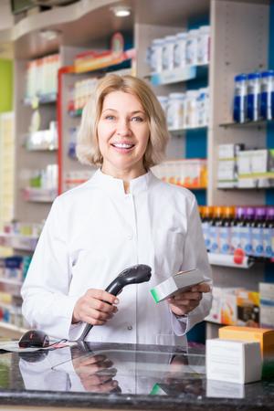 seniority: Mature positive female pharmacist posing in drugstore