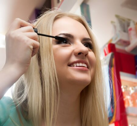 Young blonde woman choosing things for make_up and smiling