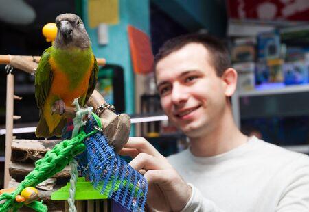 young man looks at big Senegal parrot in a pet shop