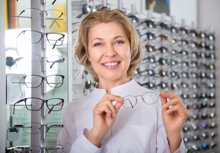 Eldery professional female ophthalmologist in optics store