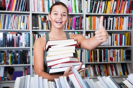 brunete: ordinary girl holding stack of books shows thump up in a bookstore