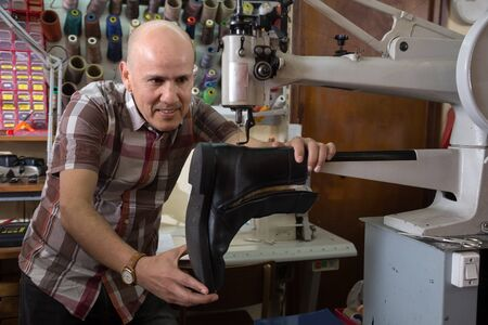 broach: senior Professional shoemaker stitching footwear on machine in shoe atelier