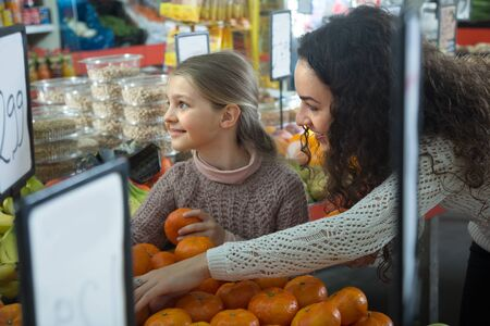 purchasers: Brunette female with blonde little girl considering mandarins at store
