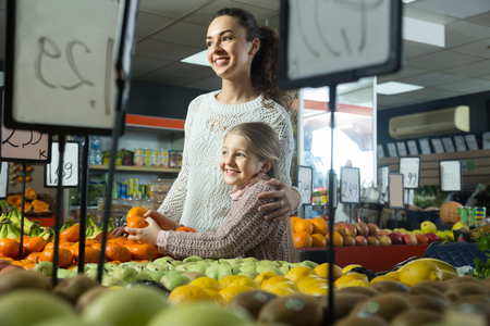 purchasers: portret beautiful blonde girl with mother choosing mandarins at store