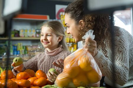portret of smiling  young woman with beautiful blonde daughter choosing mandarins at store