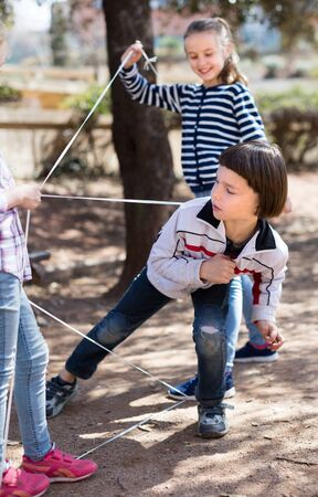 active children games. boy gently passes through the tangled rope in park Stock Photo