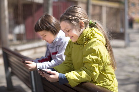 little boy with blonde girl on the bench with smartphones outdoor