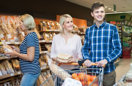 german ethnicity: young husband and wife to buy bread in the bread department of a supermarket. focus on young woman Stock Photo