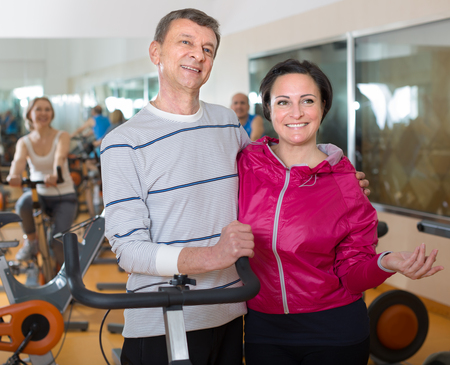 diligente: diligent elderly man and woman in background bikes at the gym