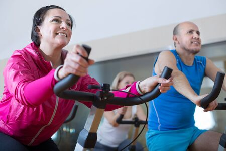 older people do sports on exercise bikes in gym