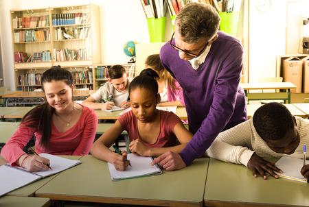 senior teacher helping African-American pupil in classroom