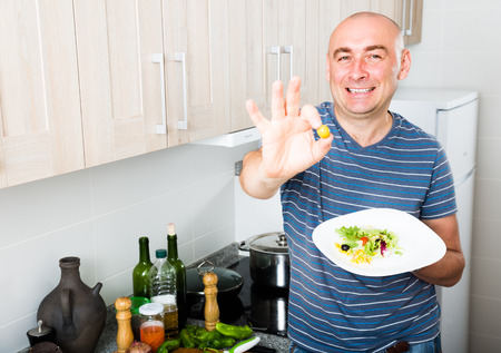 smiling male holding fingers in green olives