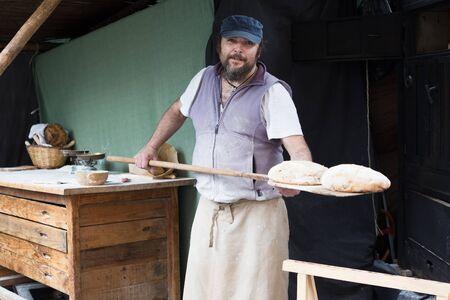 german ethnicity: baker man posing with shovel and grain dough