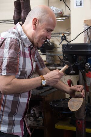 broaching: mature male specialist stitching shoes on leather sewing machine at factory Stock Photo