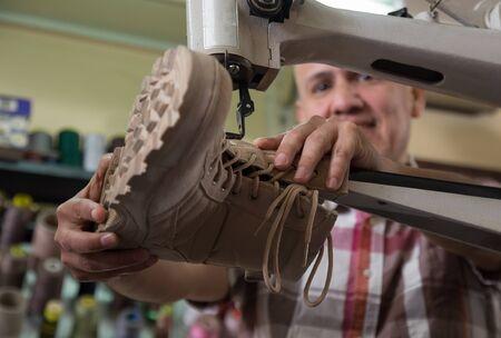 broaching: Professional craftsman stitching footwear on machine in shoe atelier Stock Photo