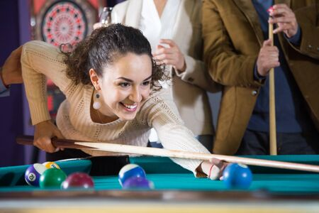 young smiling woman beats ball in billiards Stock Photo