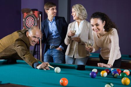 Group of friends of different generations playing billiards and smiling in billiard room. focus on mature man Banque d'images