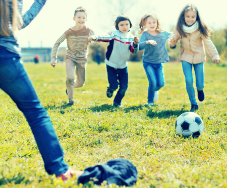 ordinary girls and boy playing soccer in park in autumn. focus on ball Stock Photo
