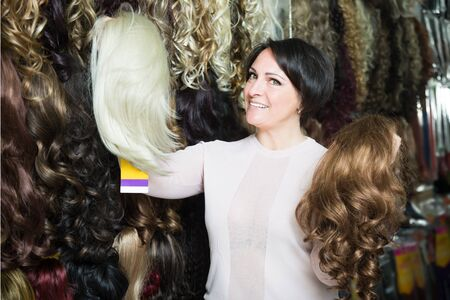 peruke: middle aged brunette woman stylish wig in store