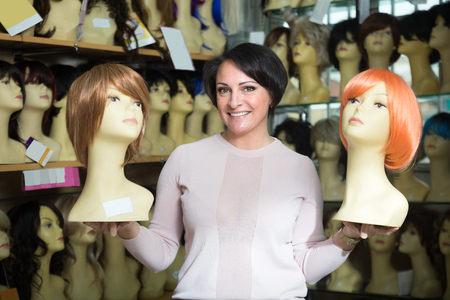 peruke: Positive middle aged female customer holding two dummy with wig in hair salon Stock Photo