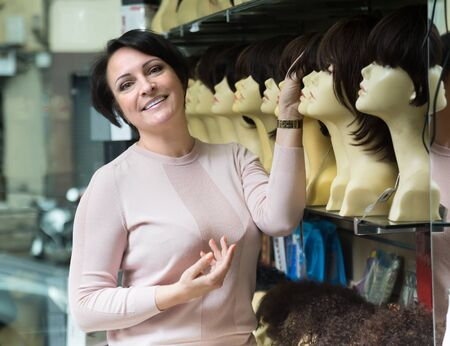 peruke: Positive middle aged female customer selecting natural hair wig in hair salon Stock Photo