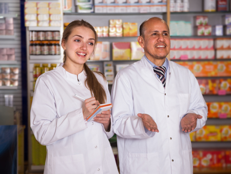 portrait of two pharmacists posing in modern drugstore Stock Photo