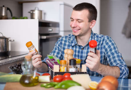 Housekeeping male chooses spices in the kitchen at home