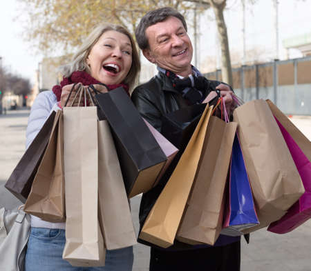 autumnn: Smiling mature husband and wife spouses with shopping bags in autumnn day