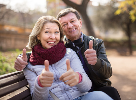 Mature family couple staying outdoor at fall day
