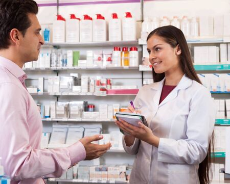 dispensary: Woman in a white robe salesman with a notebook in the pharmacy looking at visitor