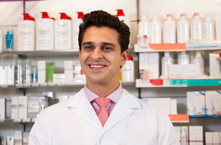 Smiling man pharmacist at the chemists shop Stock Photo